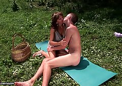 Tanned granny slams her bald pussy on an eager young cock loving it outdoor
