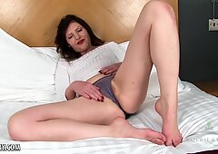 Brunette with a bush to match fingers her pussy