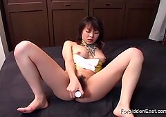 Oriental woman brings herself to orgasm on the bed